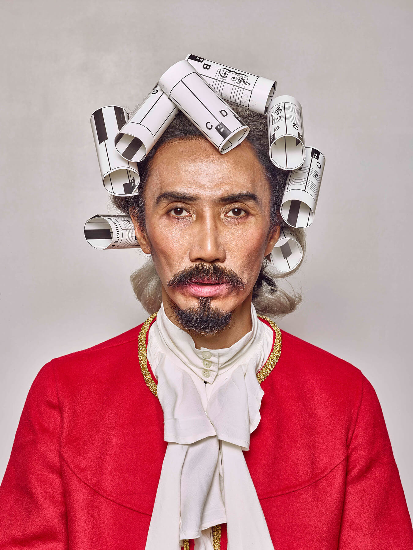 "2 Sep 2017: Derong is styled like Mozart, with rolled up printed music scores as his ""hair"""