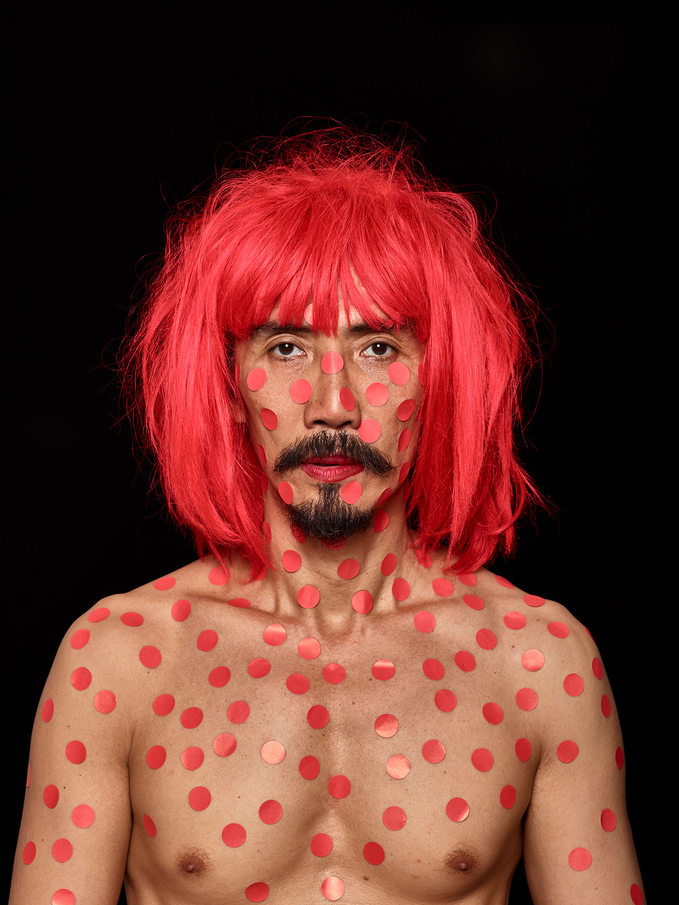 21 Aug 2017: Derong is in a red wig and has red round stickers stuck all over his bare face and body