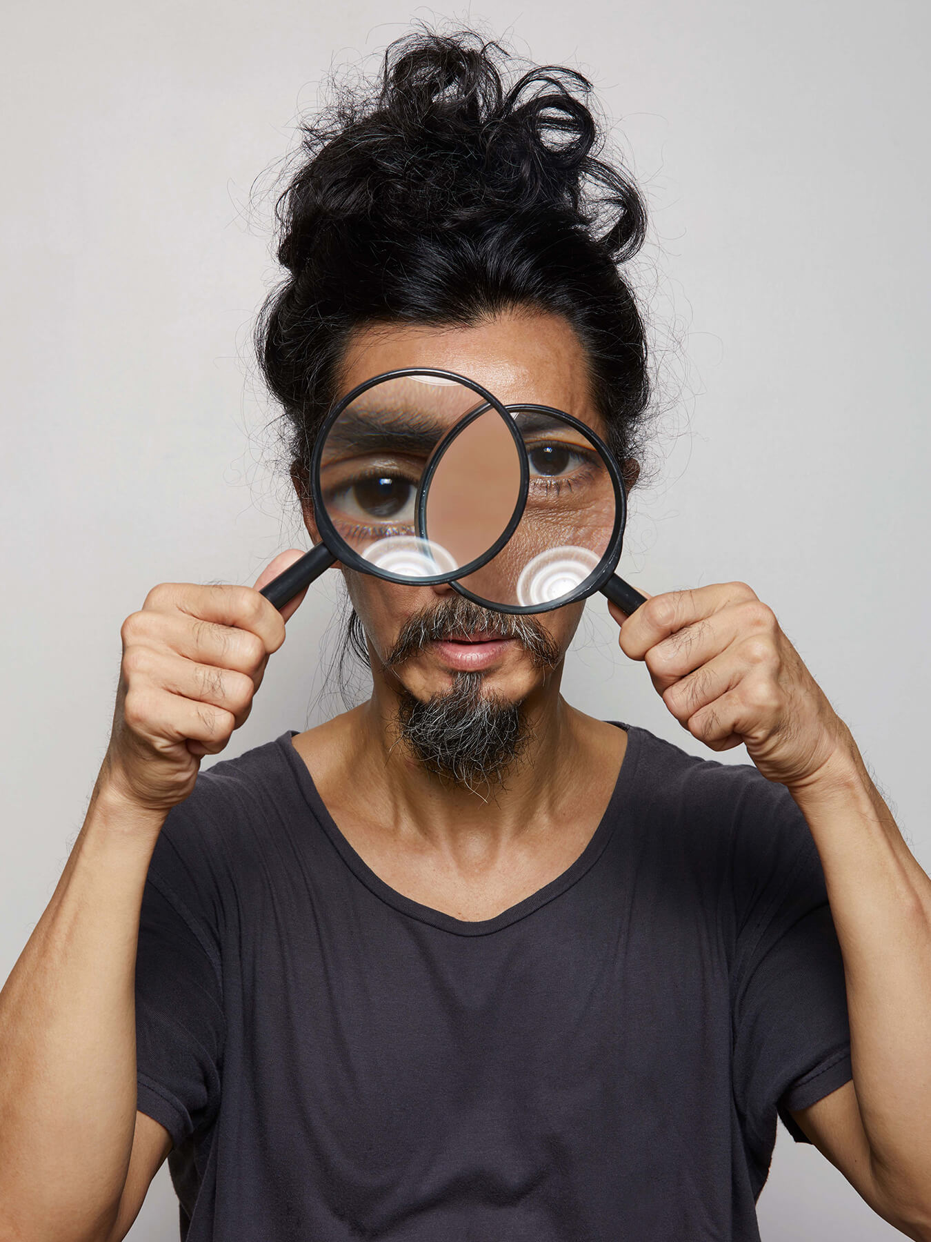 3 Oct 2017 - Seeing Double: Derong holds 2 magnifying glasses, distorting his eyes